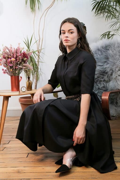Portrait de la robe Yvette noire dans un atelier parisien.